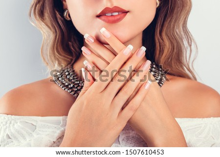 Nail art and design. Beautiful woman wearing make-up and jewellery and showing her french manicure. Beauty fashion model #1507610453