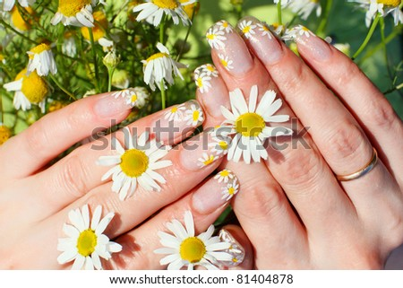 Nail art design. Woman hands with camomile flowers