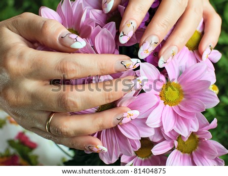 Nail art design. Woman hands with chrysanthemums flowers.
