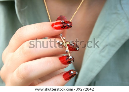 Nail-art fingers holding golden cross with necklace. - stock photo