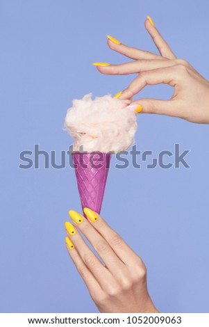 Nail Art. Hands With Colorful Nails And Cotton Sugar Ice Cream. Closeup Of Female Hands With Trendy Orange Manicure Holding Cone With Cotton Candy On Purple Background. Nail Design. High Quality