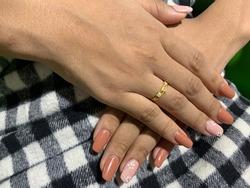Nail artist. Female hands with orange nail design on black, gray ,white on scott skirt.Female hand with orange nails, white flower painting and gold ring.Nail Salon.Spring Summer Holidays.