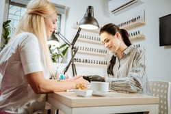 Nail artist. Pleasant dark-haired nail artist feeling good talking to her constant client while working