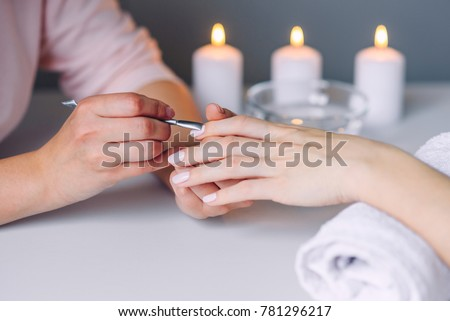Nail care. Closeup of beautiful woman hands getting manicure in spa salon. Female manicurist cleaning cuticle with professional manicure pusher tool. Cosmetic procedure. Stok fotoğraf ©