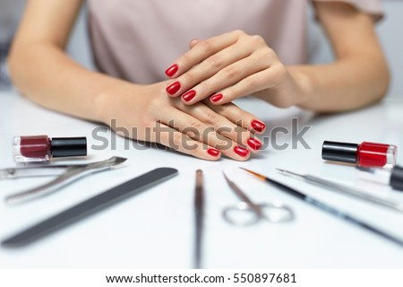 Nail Care. Closeup Of Beautiful Woman Hands Showing Perfect Nails Painted With Red Nail Polish On White Background. Female Hands Near Set Of Professional Manicure Tools. Beauty Care. High Resolution