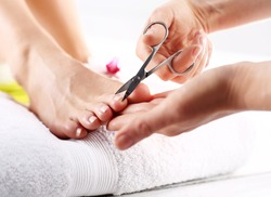 Nail clipping, cutting skins pedicure treatment. Foot care treatment and nail, the woman at the beautician for pedicure.