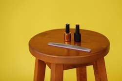 nail polish and a nail file on a chair. yellow bright background. manicure