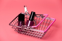 Nail Polish and cuticle trimmer in the basket of the supermarket on pink background