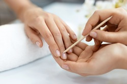 Nail Salon. Closeup Of Beautician Hands Cleaning Female Client's Nails With Orange Wooden Stick, Cuticle Pusher, Removing Cuticles In Beauty Salon. Woman Hands Nail Care And Manicure. High Resolution