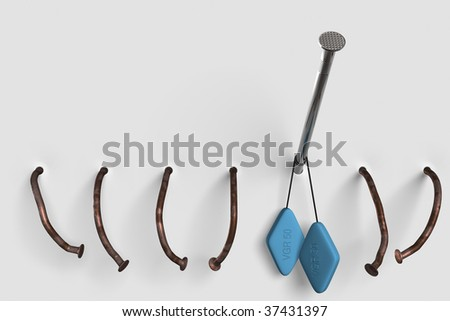 Nail with blue pills. White wall. Chrome nail and two pills in rusty eld nails environment. - stock photo