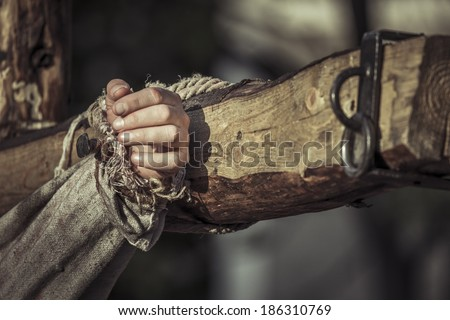 Nailed hand on wooden cross. Crucifixion of Jesus Christ.