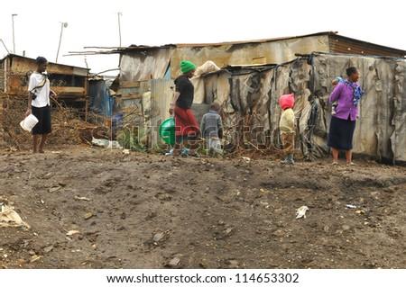 NAIROBI, KENYA-OCT. 13: Unidentified people walk in mud through the Nairobi slum Oct. 13 2011 in Nairobi, Kenya. Kibera is the largest slum in Nairobi, and the second largest urban slum in Africa