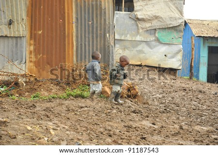NAIROBI, KENYA OCT. 13: Unidentified people walk in mud through the Nairobi slum Oct. 13 2011 in Nairobi, Kenya. Kibera is the largest slum in Nairobi, and the second largest urban slum in Africa