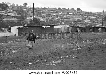NAIROBI, KENYA OCT. 13: Unidentified woman walks in mud through the Nairobi slum Oct. 13, 2011 in Nairobi, Kenya. Kibera is the largest slum in Nairobi, and the second largest urban slum in Africa
