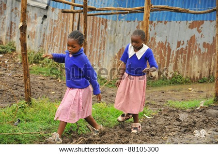 NAIROBI, KENYA- OCTOBER 13: Unidentified children walk in mud for to go school on October 13, 2011 in Nairobi, Kenya. Kibera is the largest slum in Nairobi, and the second largest urban slum in Africa