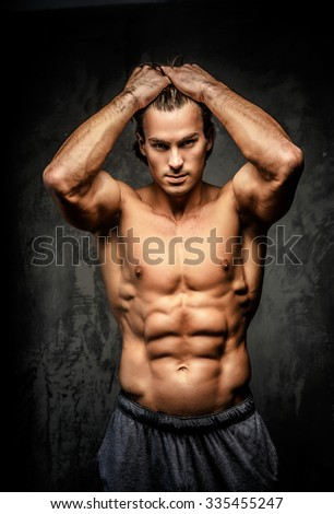 Naked bodybuilder holding his head.