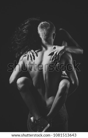 Naked couple of sexy woman in red trainers sitting on man with strong muscular body standing with back on black studio background, vertical picture