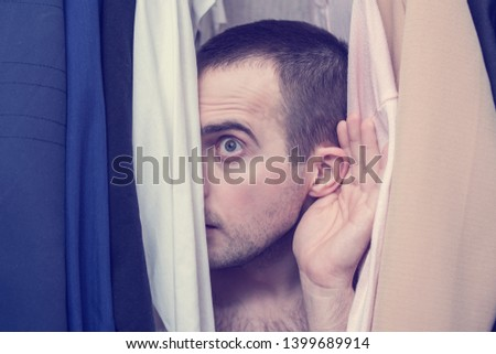 Naked man eavesdropping and hiding in the closet with clothing, portrait, close up, secret lovers concept, toned #1399689914