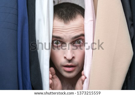 Naked man, lover hiding in the closet with clothing, afraid of being found, portrait, close up, secret lovers concept #1373215559