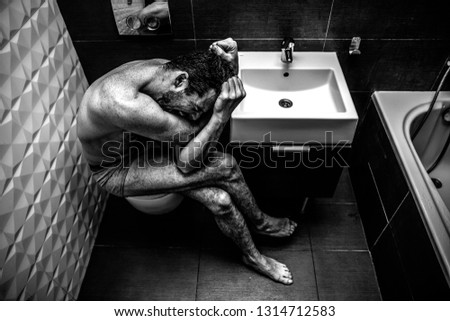 Naked man sitting in the old city toilet. Person feels terrible emotional pain and helplessness. The addict feels bad. Black and white picture.