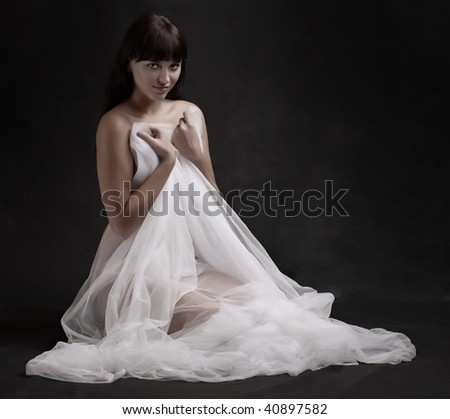 Naked sexy beautiful slenderness young woman in bridal veil on black background. Low key studio shot. Great for calendar.