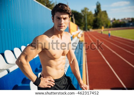 Naked sexy handsome male athlete at the stadium looking at camera