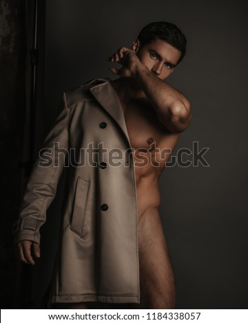 Naked sexy man with rain coat on one shoulder