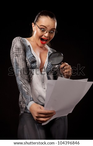Naked shocked woman covered with body paint  business suit, holding a magnyfing glass and blank documents. Concept image of sexual issues at work. High resolution studio picture on black background.