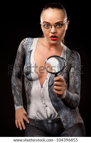 Naked shocked woman covered with body paint business suit, holding a magnyfing glass. Concept image of sexual issues at work. High resolution studio picture on black background.