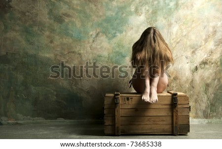 Naked  skinny woman sitting on a wooden chest