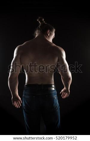 naked torso male bodybuilder athlete in the studio on a black background #520179952