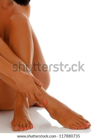 Naked woman sitting on white floor