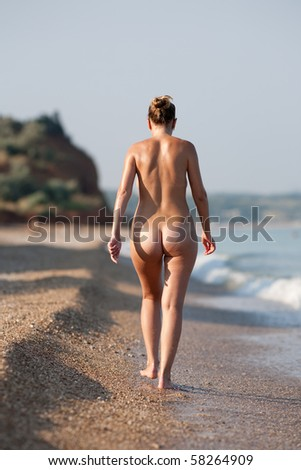 Naked woman walking along the beach