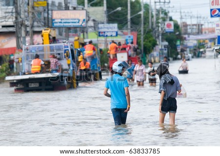 NAKHON RATCHASIMA - OCTOBER 24: People wading through the streets of the city during the worst monsoon flood in 50 years on October 24, 2010 in Nakhon Ratchasima, Thailand. - stock photo