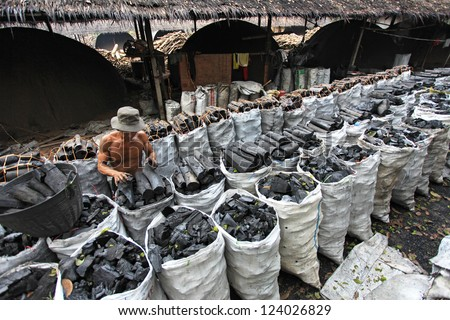 NAKHON SI THAMMARAT, THAILAND - MAY 12 : Unidentified worker in a charcoal factory packs charcoals into plastic bags for shipment on May 12, 2010 in Nakhon Si Thammarat, Thailand.