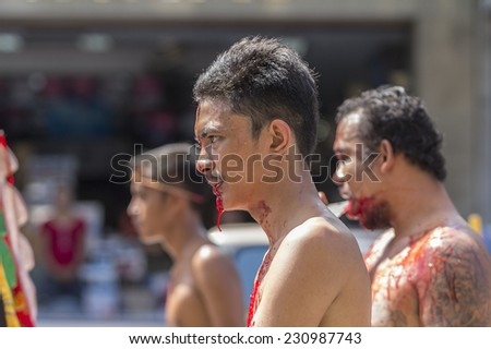 NAKHON SI THAMMARAT, THAILAND - OCTOBER 25: Taoist devotees participate in a street procession of Nakhon Si Thammarat vegetarian festival on October 25, 2014 in Nakhon Si Thammarat province, Thailand. #230987743