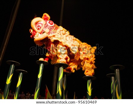 NAKHONSAWAN/ THAILAND-JANUARY 25: Kwong Siew Lion jumping on the Mei flower poles in Chinese New Year Festival on January 25, 2012 in Nakhonsawan. It hesitates for further jumping or going back.