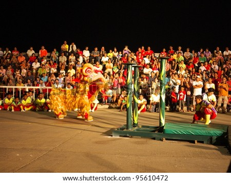 NAKHONSAWAN,  THAILAND-JANUARY 25: Kwong Siew Lion jumping on the Mei flower poles in Chinese New Year Festival on January 25, 2012 in Nakhonsawan. The lion forecasts for his power before jumping.