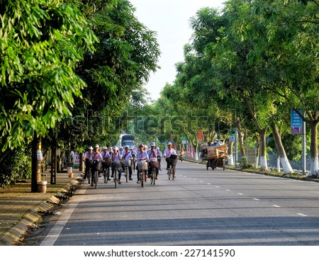Nam Dinh - VIETNAM - September 15, 2014 Children Group of students in uniform on his way home from school. Group of children students are riding a bike and was happy to talk about class.