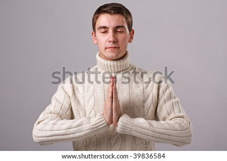 Namaste. Praying man on a gray background.