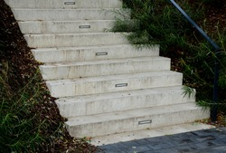 name gray monolithic concrete park bench made of concrete in the shape of round stones wooden staircase bench with staircase lighting with metal railing black lattice on the stairs, wheelchair ramp