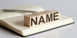 NAME sign on a wooden block on notebook background