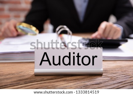 Nameplate With Auditor Title Kept On Desk In Front Of Businessman Examining The Invoices Foto stock ©