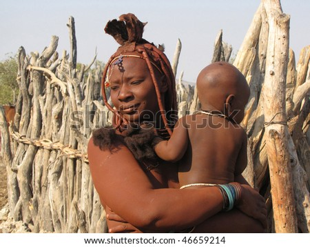 NAMIBIA, KAOKOVELD, AUGUST 29: Himba woman with her small son smiling to the camera in the village of Himba people near Opuwo in northern Namibia, August 29, 2009, Namibia
