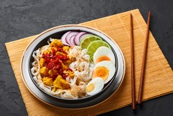 Nan Gyi Thoke in black bowl at dark slate background. Nan gyi Thohk is popular burmese cuisine dish with rice noodles, chicken breasts with spices, eggs, peanuts, lime and red onion.