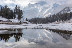 Nanga parbat mountain reflection in lake on Fairy meadows valley beautiful winter snowy landscape Karakoram Pakistan