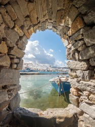 Naoussa village, in Paros island, partial view of the fishing port through a stone window of the village's castle. The name of the blue boat is