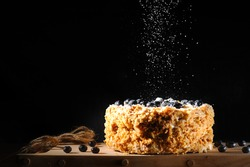 Napalion cake, pie, layered cake, puff cake with blueberry sprinkled with powdered sugar, black background. twine