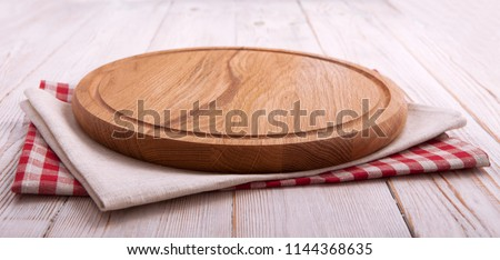 Napkin and board for pizza on wooden desk closeup. Canvas, dish towels on white wooden table background top view mock up. Selective focus.