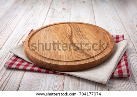 Napkin and board for pizza on wooden desk. Stack of colorful dish towels on white wooden table background top view mock up. Selective focus.